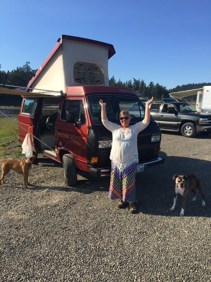 Emily Caryl Ingram standing joyfully in front of her Volkswagen Vanagon prepped for camping