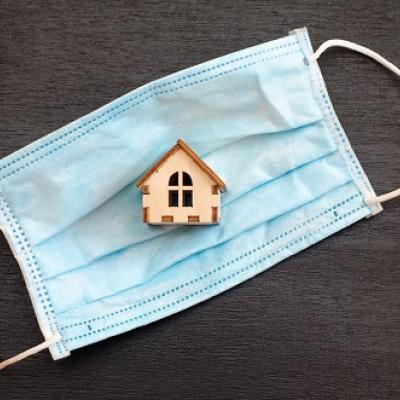 Small wooden house is inside a blue medical mask, on a black background